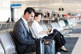 Iş adamı ve iş kadını havaalanında bilgisayar kullanarak — Stok fotoğraf
