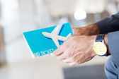 Man holding air ticket in airport — Stock Photo