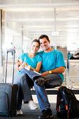 Casal jovem feliz à espera de voo — Fotografia Stock