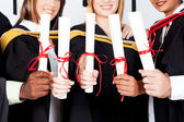 Group of graduates holding certificates — Stock Photo