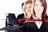Graduates holding graduation caps — Stock Photo