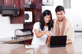 Young indian couple using computer — Stock Photo