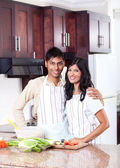 Happy young indian couple in kitchen — Stock Photo