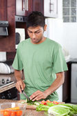 Young indian man cooking in kitchen — Stock Photo