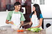 Modern indian couple cooking in kitchen — Stock Photo