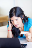 Young woman checking credit card balance — Stock Photo