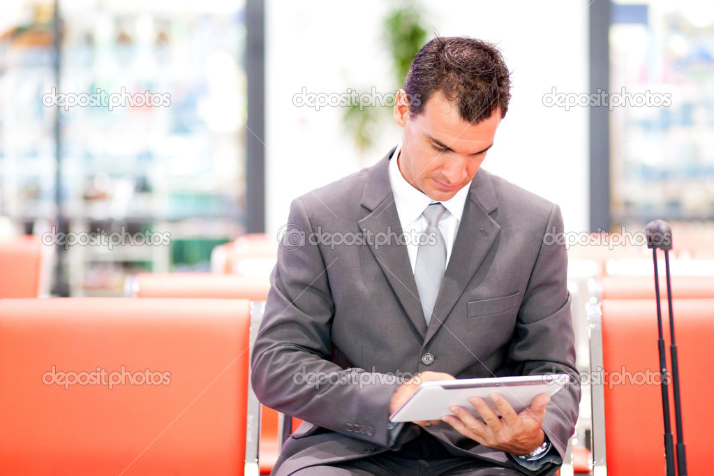 Handsome businessman using tablet at airport — Stock Photo #10422781