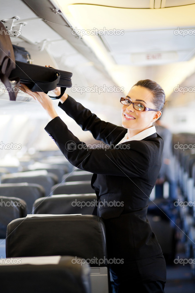 Pretty businesswoman putting her luggage into overhead locker on airplane — Stock Photo #10422831