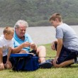 Grandpa and grandsons fishing by the lake — Stock Photo