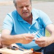Senior man putting bait on fishing hook — Stock Photo