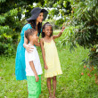 Mother and kids in litchi orchard — Stock Photo