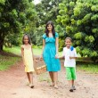 Mother and kids walking in fruit garden — Stock Photo