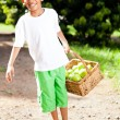 Royalty-Free Stock Photo: Boy carrying basket of apples