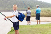 Happy little boy fishing by the lake — Stock Photo