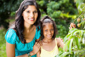 Mother and daughter in litchi orchard — Stock Photo