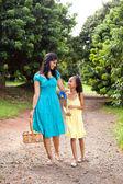 Mother and daughter walking in fruit garden — Stock Photo