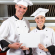 Chefs holding white board in kitchen — Stock Photo #10674478