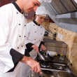 Young professional chefs in kitchen — Stock Photo #10674522