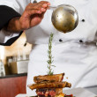 Chef adding sauce to meat dish — Stock Photo #10674530
