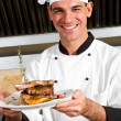 Young male chef presenting food — Stock Photo #10674537