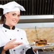 Young beautiful female chef presenting food — Stock Photo