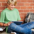 Teen boy using tablet computer in school — Stock Photo