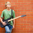 Stock Photo: Teen boy with guitar daydreaming