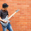 Teen boy playing guitar outdoors — Stock Photo