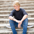 Teen boy sitting on skateboard — Stock Photo
