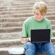 Teen boy using laptop outdoors — Stock Photo