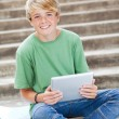 Stock Photo: Teen boy using tablet computer