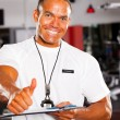 Male gym trainer giving thumb up — Stock Photo #10678661
