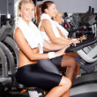 Group of girls on gym bike — Stock Photo