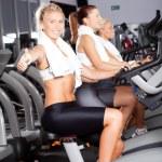 Woman giving thumb up on gym bike — Stock Photo