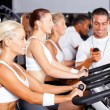 Gym trainer monitoring trainees cycling performance - Stock Photo