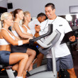 Sport coach timing cyclist in gym — ストック写真