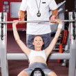 Fitness woman and personal trainer in gym — Stock Photo