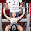 Fitness woman in gym with personal trainer - Foto Stock