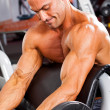 Muscular man training in gym — Stockfoto