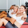 Foto Stock: Group of doing situps in gym