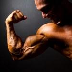 Bodybuilder posing on black background — Stock Photo