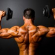 Bodybuilder training with dumbbells — Stock Photo