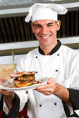 Junge männliche küchenchef präsentiert essen — Stockfoto