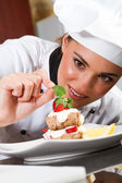 Beautiful young chef decorating dessert — Stok fotoğraf