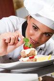Beautiful young chef decorating dessert — Stock Photo