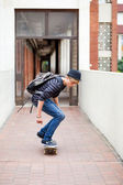 Teen boy skateboarding in school passage — Stock Photo