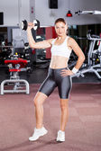 Fitness woman working out with dumbbell in gym — Stock fotografie