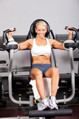 Fitness woman using peck deck machine — Stock Photo