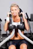 Young woman working out in gym — Stock Photo