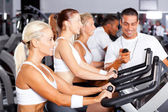 Gym trainer monitoring trainees cycling performance — Stock Photo